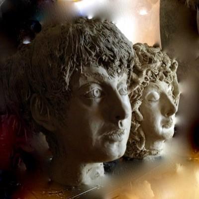 due volti in argilla che rappresentano Apollo e Medusa